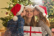 Daughter and son in Santa hats kissing mother with Christmas gift — Stock Photo