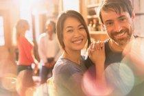 Ritratto di sorridere multirazziale coppie che abbracciano nella caffetteria — Foto stock