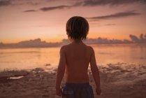 Мальчик на пляже смотрит на спокойный закат океана — стоковое фото