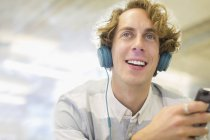 Happy young man listening to headphones — Stockfoto