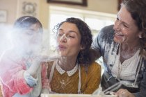 Три покоління жінок, граючи з борошна — стокове фото