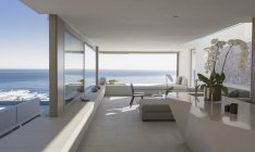 Modern, luxury home showcase interior living room with sunny ocean view — Stock Photo