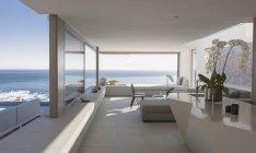 Moderno, casa de lujo escaparate sala de estar interior con vista al mar soleado - foto de stock