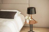 Lampe und Rosenstrauß auf dem Nachttisch — Stockfoto