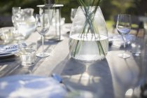 Vase and place settings on sunny patio table — Stock Photo