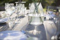 Vaso y cubiertos en la mesa de patio soleado - foto de stock