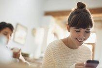 Envoyer des SMS de jeune femme souriante avec téléphone portable — Photo de stock