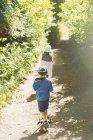 Мальчик и девочка идут по дорожке вдоль солнечного дерева в парке — стоковое фото
