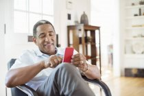 Senior man text messaging with cell phone in living room — Stock Photo