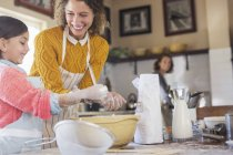 Happy caucasian mother and daughter baking together — Stock Photo