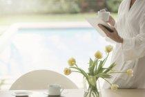 Mujer en bata de baño tomando café y el uso de tabletas digitales en junto a la piscina - foto de stock