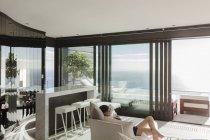 Женщина, расслабляясь в современной гостиной с видом на океан — стоковое фото