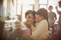 Молоді жінки друзів, прийняття selfie з камери телефону в квартирі — стокове фото