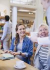 Barista serving coffee to mother and daughter in cafe — Stock Photo