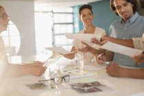 Creative business people brainstorming, passing paperwork in conference room meeting — Stock Photo