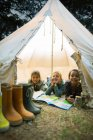 Children smiling in tent at campsite — Stock Photo