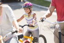 Portrait of smiling girl riding bicycle with parents — Stock Photo