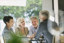 Smiling couples talking and dining at restaurant table — Stockfoto