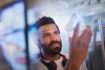 Concentré, entrepreneur innovateur de mâle examinant prototype de triangle de verre — Photo de stock
