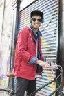 Человек толкает велосипед по городской улице — стоковое фото