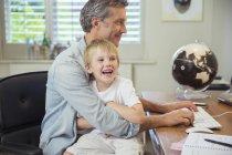 Отец держит сына и использует компьютер — стоковое фото