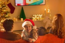 Portrait smiling girl in Santa hat watching TV with parents in Christmas living room — Stock Photo