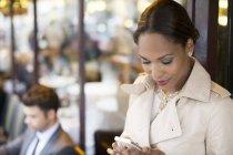 Donna d'affari che utilizza il telefono cellulare al caffè marciapiede — Foto stock