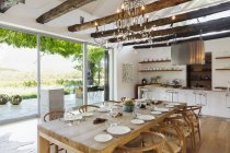 Chandelier over dining table in modern house — Stock Photo