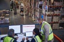 Manager che lavorano incontro al laptop e computer nel magazzino di distribuzione — Foto stock