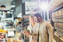 Junges Paar kauft auf Markt ein — Stockfoto