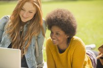 Щасливі молодих жінок, використовуючи ноутбук у парку — стокове фото