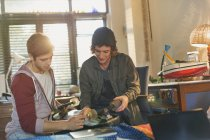 Young male friends examining skateboard — Stock Photo