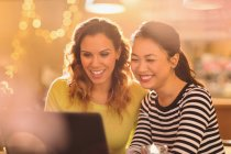 Улыбаясь женщин друзей с помощью ноутбука — стоковое фото