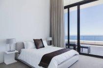 Bed and lamps in modern bedroom overlooking ocean — Stockfoto