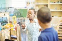 Studierende, die prüfen Vogelkäfig im Klassenzimmer — Stockfoto