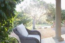 Плетеное кресло на тихом патио — стоковое фото