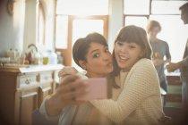 Amigos jóvenes juguetones tomando selfie con cámara de un teléfono haciendo una cara - foto de stock