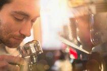 Close up barista smelling espresso grounds at espresso machine — Stock Photo