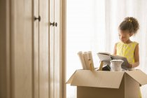 Young girl reading book near moving box — Stock Photo