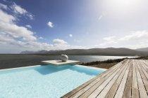 Sunny tranquilla piscina a sfioro moderna con vista sull'oceano — Foto stock