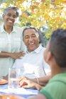 Grand-parents et petit-fils riant à la table de patio — Photo de stock