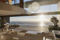 Современная гостиная с видом на океан на закате — стоковое фото