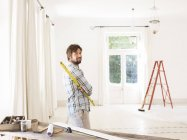 Man overlooking living space near construction materials — Stock Photo