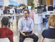 Бизнесмен улыбается на встрече в современном офисе — стоковое фото