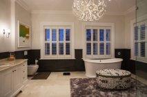 Badewanne und moderner Kronleuchter im Luxus-Badezimmer in der Nacht — Stockfoto