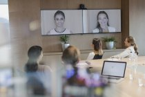 Business people talking on monitors in video conference — Stock Photo