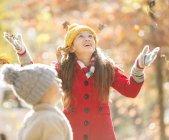 Menina jogando folhas de outono no parque — Fotografia de Stock