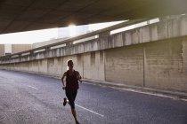 Female runner running into urban tunnel — Stock Photo
