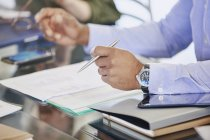 Cropped image of businessman holding pen over paperwork in meeting — Stock Photo