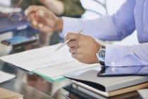 Обрезанный образ бизнесмена, держащего ручку над бумагами на встрече — стоковое фото